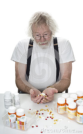 Sênior com lotes das prescrições e um punhado dos comprimidos