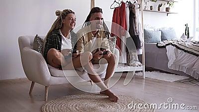 Słodka młoda para chłopak i dziewczyna grają w wideo trzymając bezprzewodowe joysticks siedząc na białym małym zdjęcie wideo
