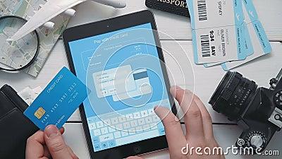 ` S путешественника взгляд сверху вручает оплачивать для билетов самолета на линии используя цифровую таблетку и кредитной карточ видеоматериал