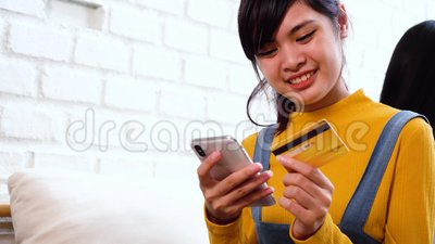 20s teenager Asian woman holding credit card and mobile phone in cozy white room. Confidently secure mobile online payment and purchase concept stock footage