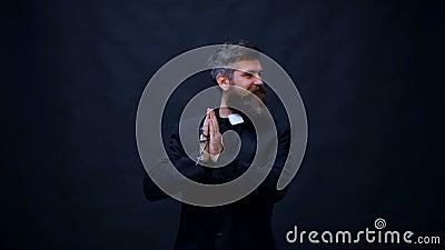 Sacerdote cristiano joven sobre el baile aislado del fondo feliz y alegre, mudanza sonriente casual y confiada almacen de video