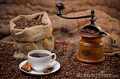 Sack of coffee beans, white cup and coffee grinder