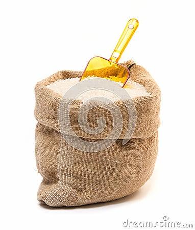 Saco do arroz e colher plástica transparente