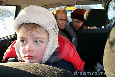 Sad boy in family car