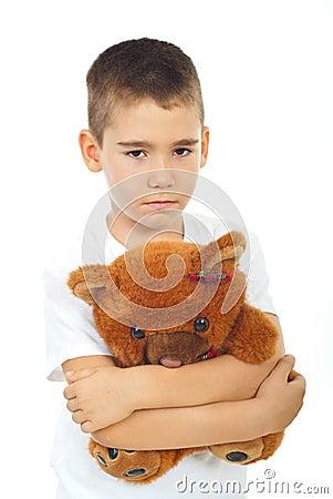 Sad boy holding teddy bear