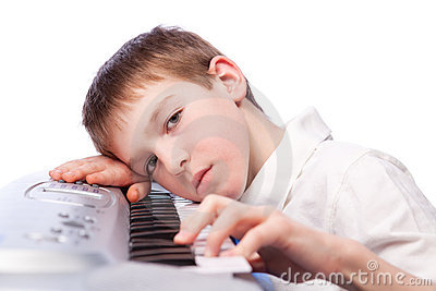 Sad boy plays piano
