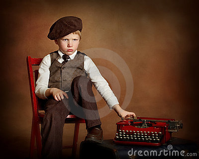 Sad boy with typewriter in chair