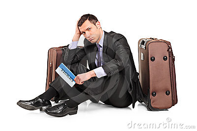 Sad business traveler seated next to a suitcase