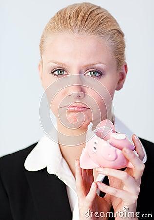 Sad business woman with broken piggybank