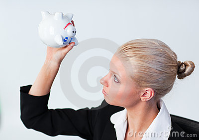 Sad Business woman looking into Piggy Bank