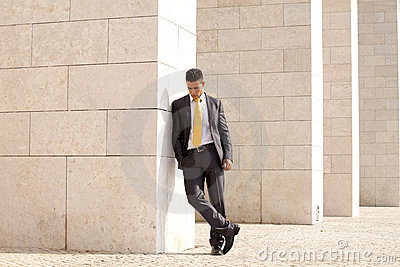Sad businessman relaxing next to some wall