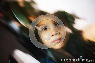 Sad child looking through window