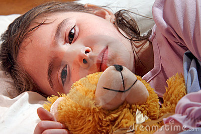 Sad girl in bed with teddy