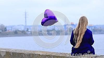 Sad girl with broken heart holding heart balloon stock video