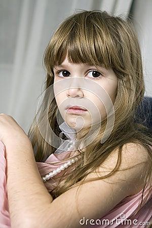 Sad girl with brown eys sitting on sofa