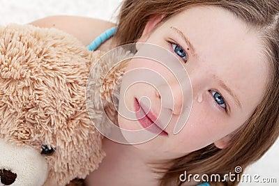 Sad girl holding teddy bear and crying