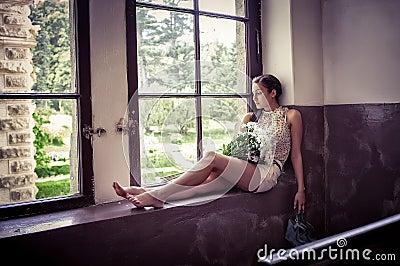 Sad girl near a window