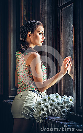 Sad girl near a window