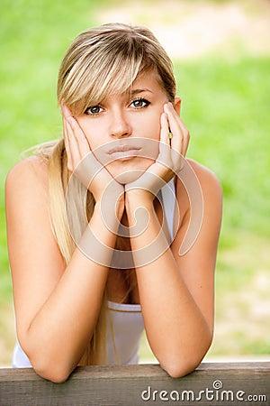 Sad girl sits on bench