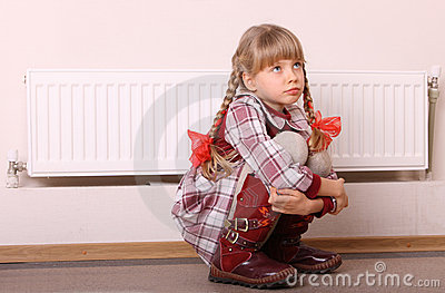 Sad girl sitting near heater. Children problem.