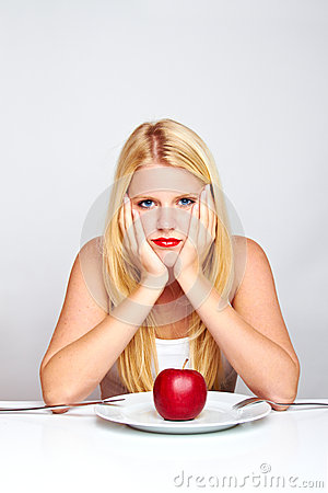 Sad healthy woman with apple