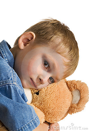 Sad kid embraces a teddy