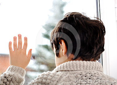 Sad kid on window and winter snow