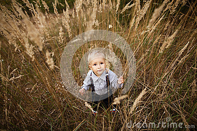 Sad little boy in high grass