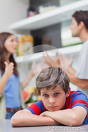 Sad little boy listening to his parents arguing