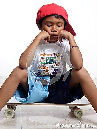 Sad little boy sitting on his skateboard