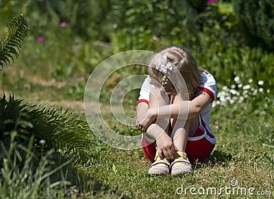 Sad little girl in garden