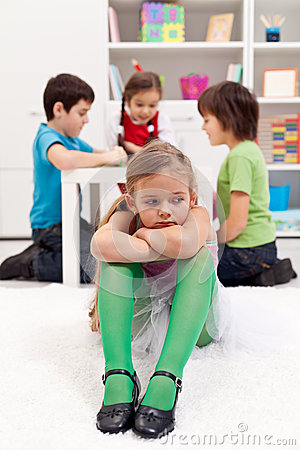Sad little girl sitting excluded by friends