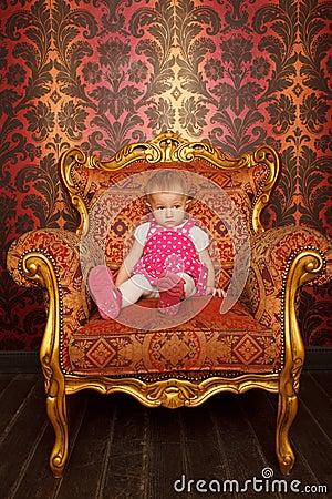 Sad little girl sitting in old armchair