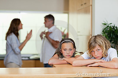 Sad looking siblings with arguing parents behind them