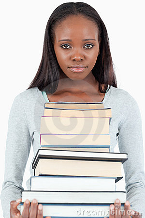 Sad looking young woman with pile of books
