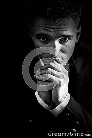 Sad man in the dark praying to God