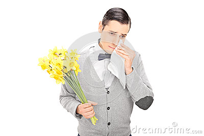 Sad man holding bunch of flowers and crying