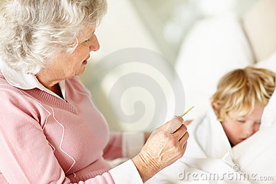 Sad mature woman reading temperature of a sick child