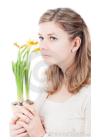 Sad pensive woman smelling at flowers