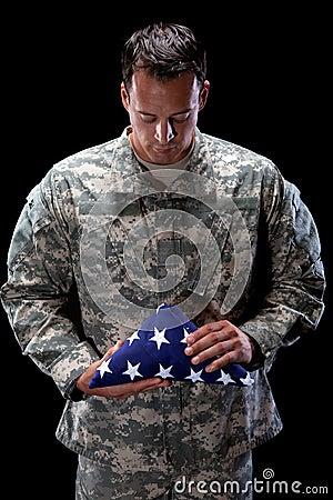 Sad soldier holds a Flag