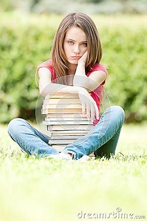 Sad student girl sitting near pile of books