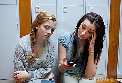 Sad student showing a text message to her friend