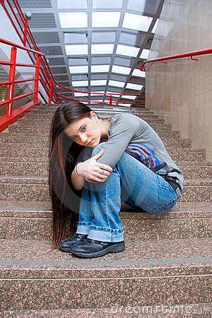 Sad teen girl on school stairs
