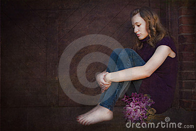 Sad teen with violet bouquet