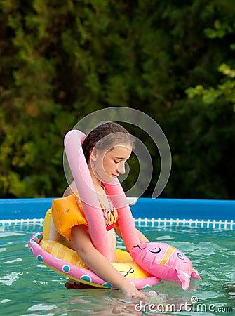 Sad teenage girl playing alone in the pool