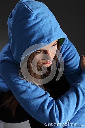 Sad teenager girl alone on floor in blue hoodie