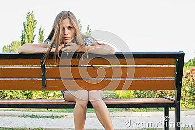 Sad teenager on park bench