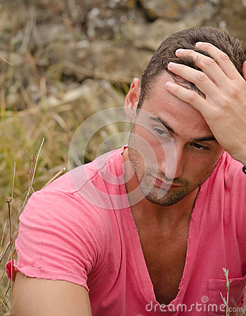 Sad or thoughtful handsome guy holding his head