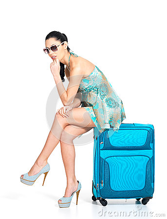 Sad tourist woman seated next to a suitcase