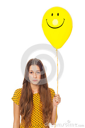 Sad woman holding smiley face balloon